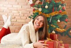 在地板上的俏丽的妇女谎言在圣诞树和举行下在手上提出 图库摄影