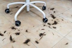 在地板上的修剪头发在扶手椅子下的一个发廊 免版税库存图片