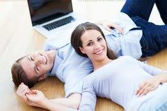 在地板上的夫妇与膝上型计算机 库存图片