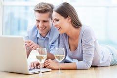 在地板上的夫妇使用膝上型计算机 免版税库存照片