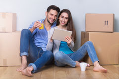 在地板上的夫妇在移动的箱子旁边 免版税库存图片