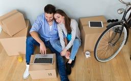 在地板上的夫妇在移动的箱子旁边 免版税库存照片