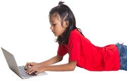 在地板上的女孩与膝上型计算机v 库存图片