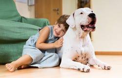 在地板上的好女孩小孩与狗 免版税图库摄影