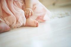 在地板上的小婴孩与在她的大脚趾的拉长的兴高采烈的面孔 库存照片
