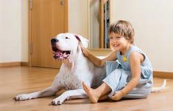 在地板上的小微笑的女孩与狗 免版税库存图片