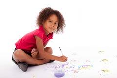 在地板上的小的非洲亚洲女孩绘画 免版税库存照片