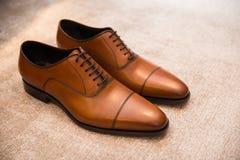 在地板上的布朗皮革经典男性鞋子 免版税库存图片