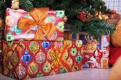 在地板上的当前箱子与一棵圣诞树在背景中 库存照片