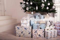 在地板上的当前箱子与一棵圣诞树在背景中 库存图片