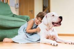 在地板上的微笑的女孩小孩与狗 库存图片