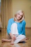 在地板上的微笑的美好的白肤金发的开会 图库摄影