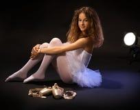 在地板上的微笑的芭蕾学生 免版税库存照片