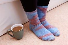 在地板上的热的饮料由在袜子的脚 免版税库存照片