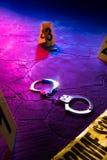 在地板上的犯罪现场手铐在晚上 图库摄影