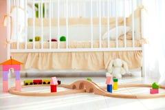 在地板上的玩具在有小儿床的晴朗的婴孩卧室在背景 免版税库存照片