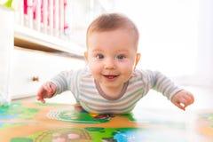 在地板上的男婴爬行 库存照片