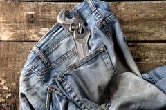 在地板上的肮脏的牛仔裤与在口袋的工具 库存图片