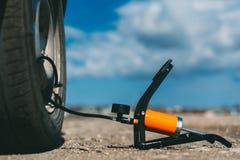 在地板上的脚踏泵在汽车和轮子旁边 免版税库存照片