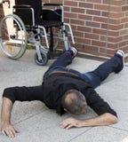在地板上的被削弱的人在落在轮椅外面以后 库存照片