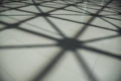 在地板上的阴影从钢结构屋顶天花板由金属和玻璃制成 库存照片