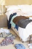 在地板和旅馆床上驱散的衣裳 免版税图库摄影