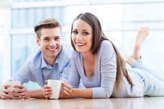 在地板饮用的咖啡的夫妇 库存照片