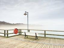 在地标渔码头的有薄雾的黄昏,码头栏杆 木痣 免版税库存照片