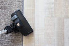 在地毯和木镶花地板的现代吸尘器 库存照片