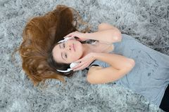 在地毯放置的妇女听耳机 免版税库存图片