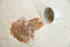从在地毯的咖啡杯溢出 图库摄影