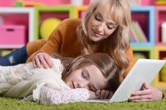 在地毯的妈妈和女儿谎言 免版税库存图片