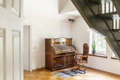 在地毯的扶手椅子在白色客厅内部的木钢琴旁边与植物和台阶 实际照片 图库摄影
