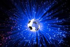 在地球地球的足球在蓝色背景  免版税库存照片