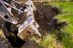 在地球工作期间的挖掘机桶开掘的坑 免版税图库摄影