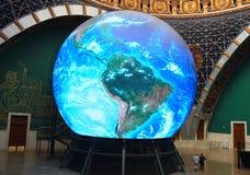 在地球的巨大的地球的旁边两个人 图库摄影