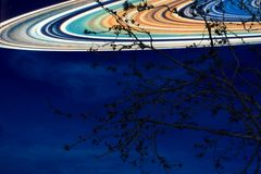 在地球附近的土星在夜空后面剪影干燥树 免版税图库摄影