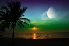 在地球附近的土星在海和日落的夜空 图库摄影