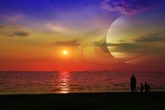 在地球附近的土星在海和日落的夜空 免版税图库摄影