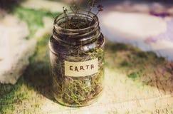 在地理地图的地球和在一个玻璃瓶子的干草本,作为环境和世界旅行的标志 库存照片
