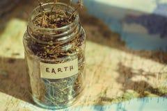 在地理地图的行星地球和在一个玻璃瓶子的干医药草本,作为环境和旅行的标志 免版税库存照片