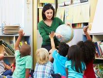 在地理类的基本的学生与老师 免版税库存图片