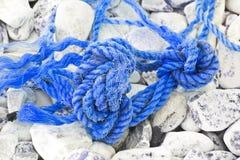 在地面上放弃的老损坏的被缠结的塑料绳索 免版税库存照片
