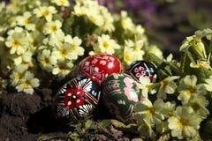 在地面上的乌克兰全国krashanki谎言以黄色和桃红色报春花为背景 在春天花附近的复活节彩蛋 图库摄影