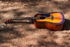 在地面上的吉他layong在秋天中午 免版税库存图片