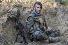 在地面上的战士与枪 免版税库存图片