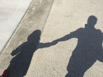 在地面上的手拉手父亲和女儿阴影 免版税库存图片