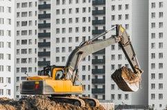 在地面上的挖掘机工作在多楼层房子背景  免版税库存图片