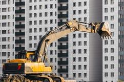 在地面上的挖掘机工作在多楼层房子背景  图库摄影
