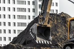 在地面上的挖掘机工作在多楼层房子背景  免版税库存照片